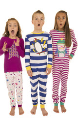 three children wearing winter pajamas with a startled facial exp