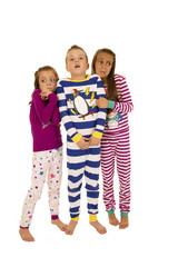 Three children standing wearing Christmas pajamas frightened exp