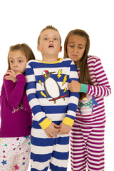 Three children wearing winter pajamas with frightened expression