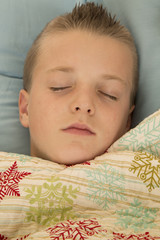 Cute young boy asleep under a snowflake blanket peace