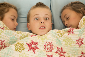Funny expression on boys face between two cousins in bed
