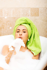 Woman blowing a foam, relaxing in bath