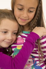 Portrait of two young girls hugging wearing pajamas