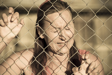 Devastatetd Crying woman at prison fence
