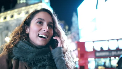 Attractive woman talking on her phone in the city at night