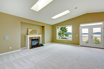 Empty spacious living room with walkout deck and fireplace.
