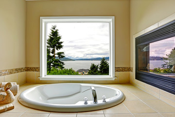 Luxury bathroom with fireplace and bay view