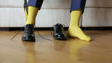 The man in a yellow socks wears shoes to tie shoelaces
