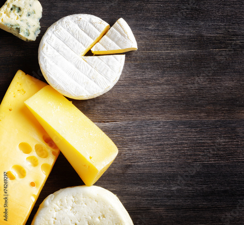 Staande foto Zuivelproducten Different types of cheese on a wooden board