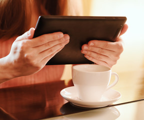 Young woman using tablet computer in cafe