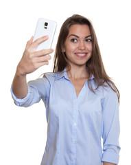 Frau mit langen braunen Haaren macht ein Selfie