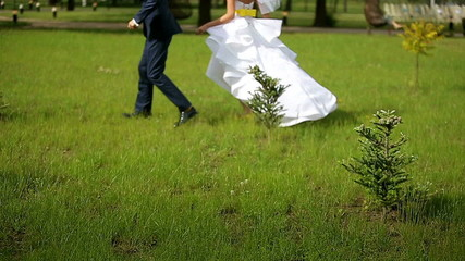 The bride and groom run one after the other slow motion
