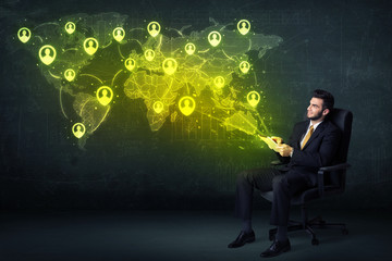 Businessman in office with tablet and social network world map