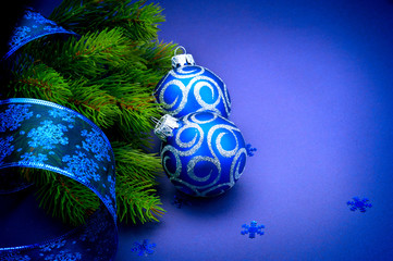 Christmas blue baubles with ribbon over blue background