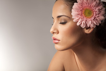 Profile of young beautiful young woman with gerbera