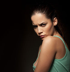 portrait of beautiful angry woman on a dark background