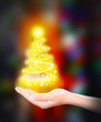 Christmas concept. Female hand with lights in shape fir tree