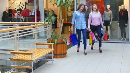 Two beautiful girls with shopping bags goes on shopping center