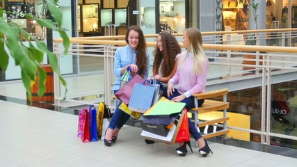 Two beautiful girls with shopping bags watch purchase on