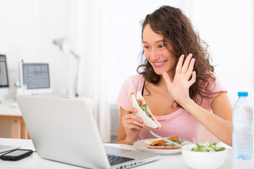 Young attractive student  eating sandwich while working
