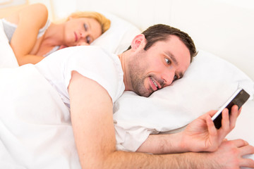 Young attractive man sending text in a bed