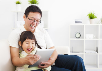 happy father using tablet pc with little girl