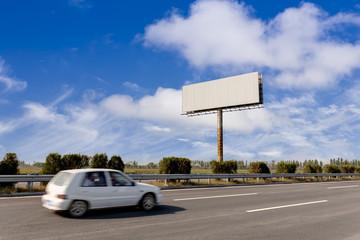 Blank billboard and blurred vehicle