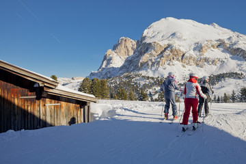 Skiers looking over the mountains and slopes. Dolomites, Italy