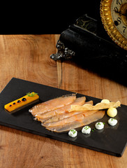 Fine dining, smoked salmon with mango jelly on black slate