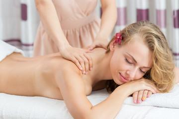Woman having massage on her shoulder in SPA salon