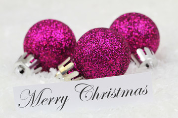 Merry Christmas card with purple baubles on snowy surface