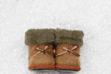 Felt booties on snowy surface with copy space