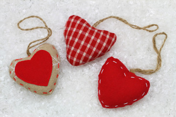 Three red hearts on snowy surface