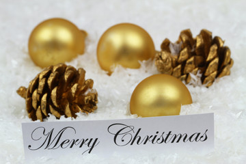 Merry Christmas card with golden baubles and pine cones