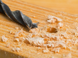 Wood drill on wooden surface with chips