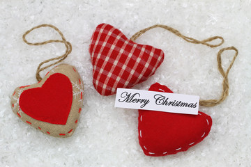 Merry Christmas card with three red hearts on snowy surface