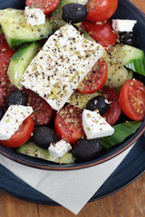 Greek salad in a deep blue bowl.