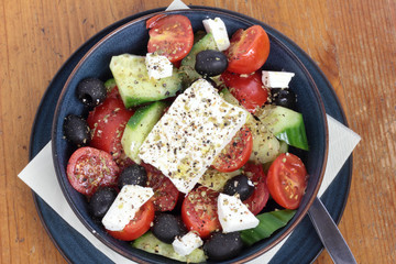 Greek salad in a deep blue bowl.