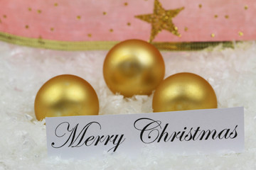 Merry Christmas card with golden baubles and red ribbon