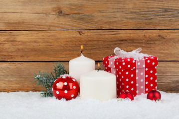 christmas red gift, candle with snow, on wooden background