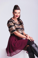 Beautiful young fashion woman smiling while sitting