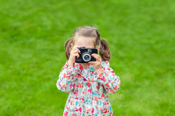 cute little girl holding camera and taking photograph outdoors.