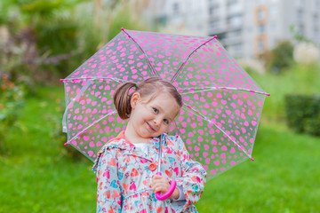 smiling liitle cute girl with her umbrella in park