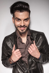 casual man smiling while pulling his leather jacket.