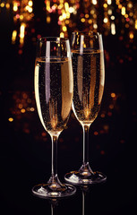 Two flutes of champagne on dark bokeh background