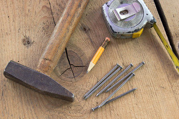 Old used carpentry tools on wooden background