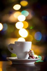 Tazzina di caffè con sfondo di luci natalizie