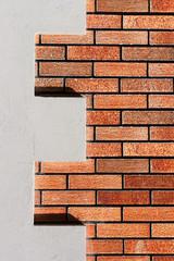 Concrete E letter on a fake brick wall