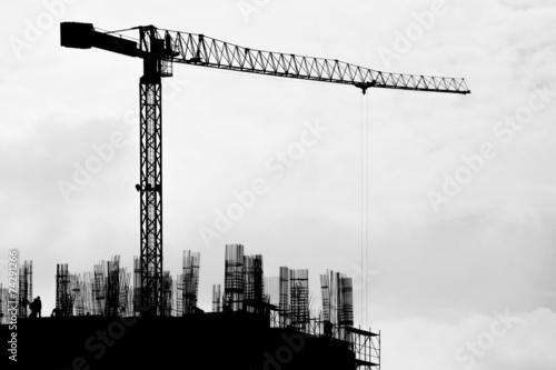 Leinwandbild Motiv Building in construction and a hoisting crane at dusk.