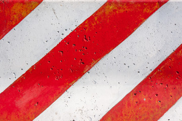 Red and white striped concrete road barrier texture.